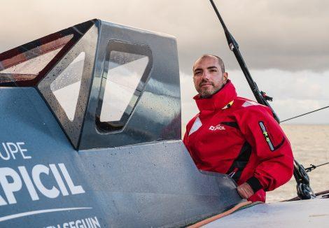 Damien Seguin skipper à bord de son bateau Apicil en train de regarde l'horizon