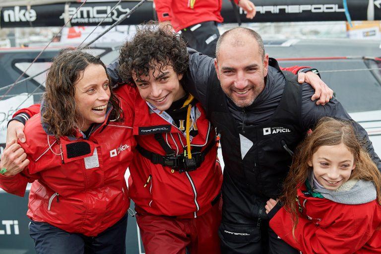 Photographie de Damien Seguin avec sa femmes et ses enfants devant son bateau à son retour du Vendée Globe
