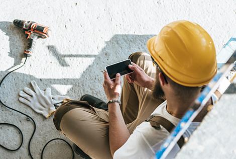 2 Un ouvrier avec son casque sur un chantier utilise son téléphone portable pour aller voir son espace client depuis l'application mobile MBTP
