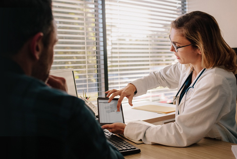 2 Une femme médecin explique à un patient homme ce que le coût d'hospitalisation va lui coûter et l'offre MBTP HOSPIT proposé par la MBTP