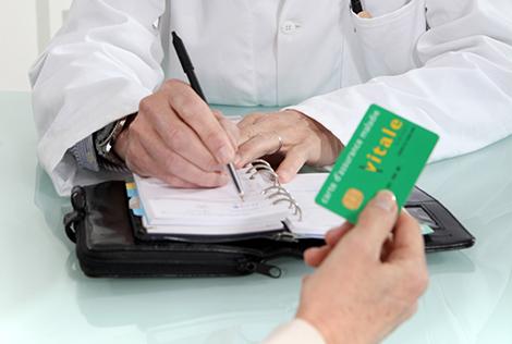 2 Photographie d'une main tenant une carte vitale de la sécurité sociale avec les mains d'un médecin écrivant dans un agenda dans le cadre du plafond mensuel de la sécurité sociale en 2021