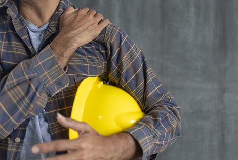 2 Ouvrier qui tient son casque dans ses mains et qui appui sur son épaule pour évoquer une douleur de TMS