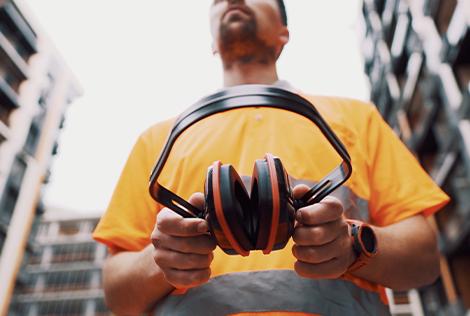 2 Photographie d'un ouvrier de chantier qui tient son casque anti-bruit dans ses mains