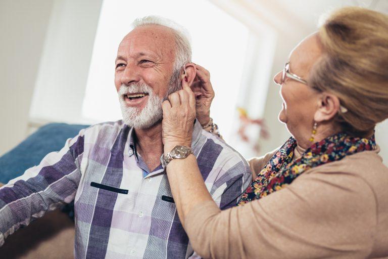 Deux personnes âgées. La femme aide l'homme à installer son appareil auditif dans on oreille gauche.
