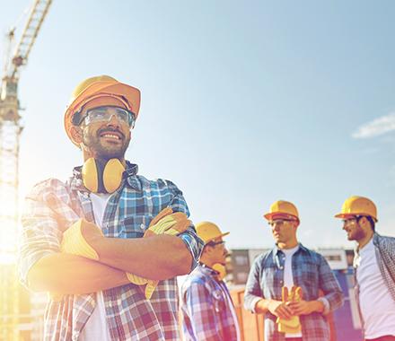 Un ouvrier en premier plan sourit et 3 ouvriers derrière lui discutent ensemble au milieu d'un chantier avec leurs casques, lunettes et gants de protections dans le cadre de la présentation des valeurs et de l'engagement de la complémentaire santé MBTP
