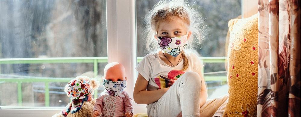 Photographie d'une petite fille masquée avec ses poupées aussi masquées pour évoquer les troubles psychologiques des enfants durant la crise sanitaire du covid19 et des séances de psychologue prévus par l'Assurance Maladie