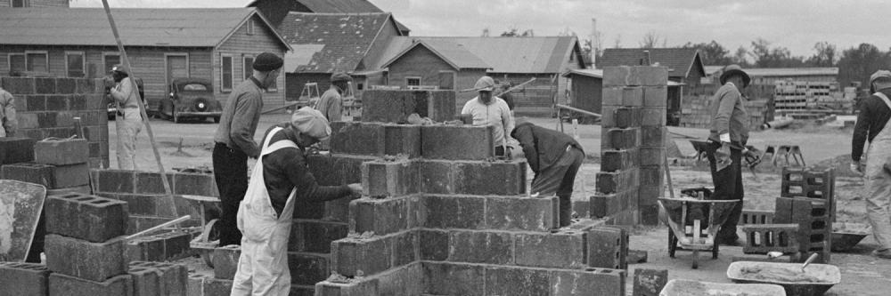 Photographie en noir et blanc d'ouvrier maçon sur une chantier de construction dans les années 80
