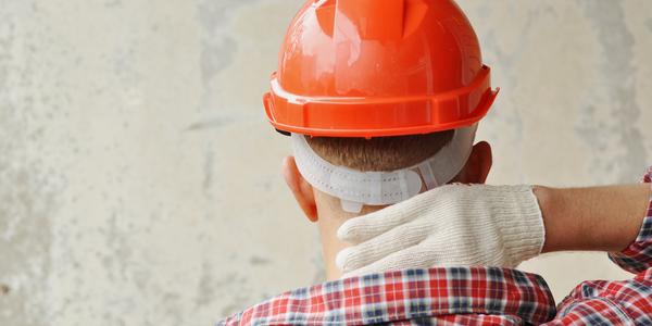 Photographie d'un ouvrier de dos avec son casque et ses gants qui se frotte la nuque pour évoquer une douleur TMS