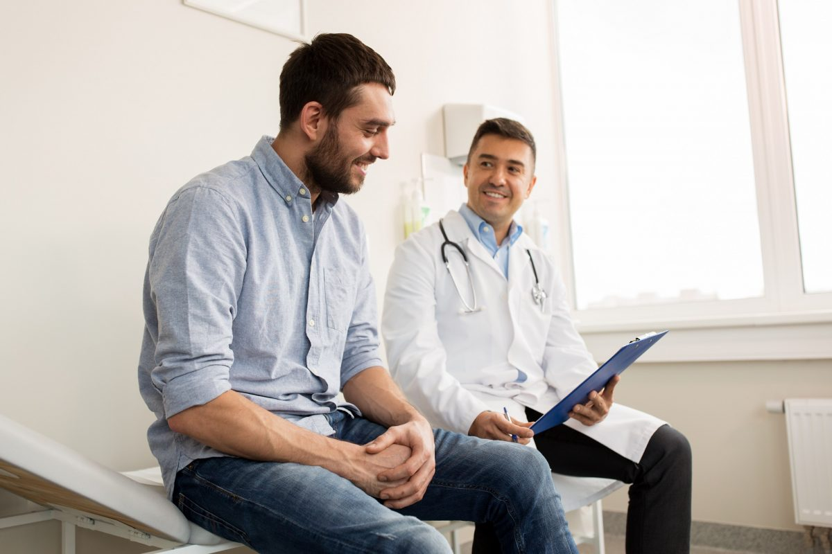 2 Un patient et un médecin discutent sur le coût d'hospitalisation assis sur une table dans un cabinet médical