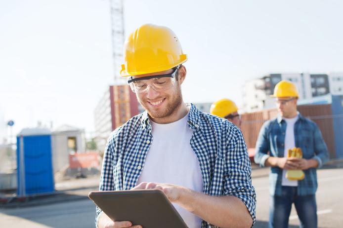 2 Plusieurs ouvrier sur un chantier dont un avec une tablette qui récupère sa carte de tiers payant dématérialisée